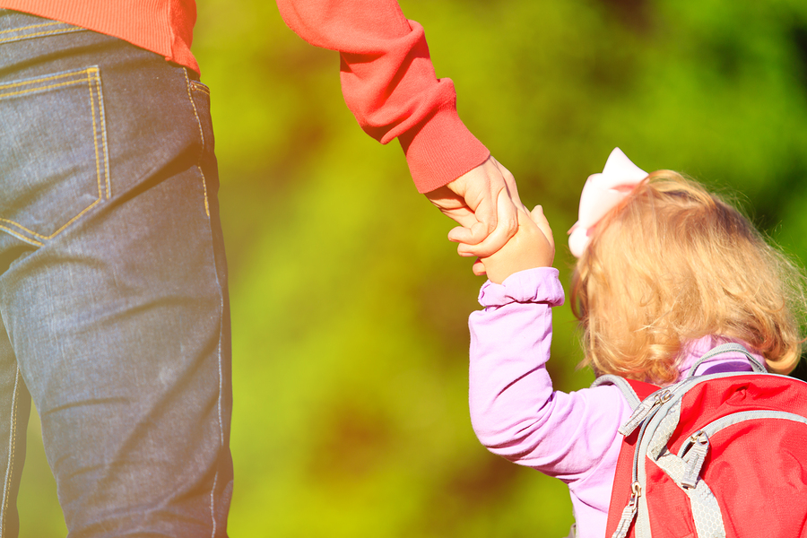 Mother holding hand of little daughter with backpack outdoors